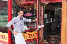 24 Apr 2013, Calgary, Alberta, Canada --- Portrait of male business owner opening diner door --- Image by © Hero Images/Hero Images/Corbis