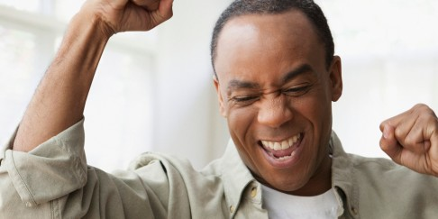 African man looking at laptop and cheering