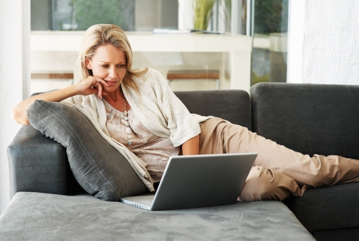 Portrait of a pretty relaxed middle aged woman using laptop on couch