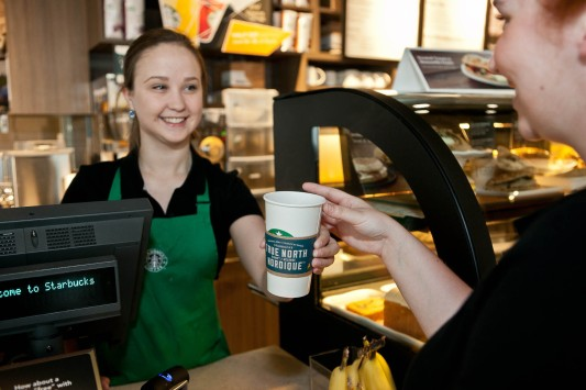 Perfectly timed for Canada Day, Starbucks barista, Jessica Roberts serves a cup of new Starbucks True North Blend™ Blonde Roast coffee in St. John's, Nfld. - the first Starbucks coffee in the world named by customers. (CNW Group/Starbucks Coffee Company)