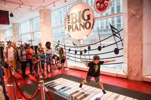 """NEW YORK, NY - JULY 14: Children play on the """"Big Piano,"""" made famous by the movie Big, in FAO Schwarz toy store on July 14, 2015 in New York City. The famed toy store will close it's doors for good July 15, and it's its owner, Toys """"R""""Us, is said to be looking for another location after rent at its current address was deemed too high. (Photo by Andrew Burton/Getty Images)"""